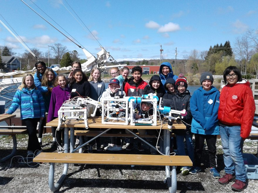 Class  with remotely operated vehicles they made on the picnic table