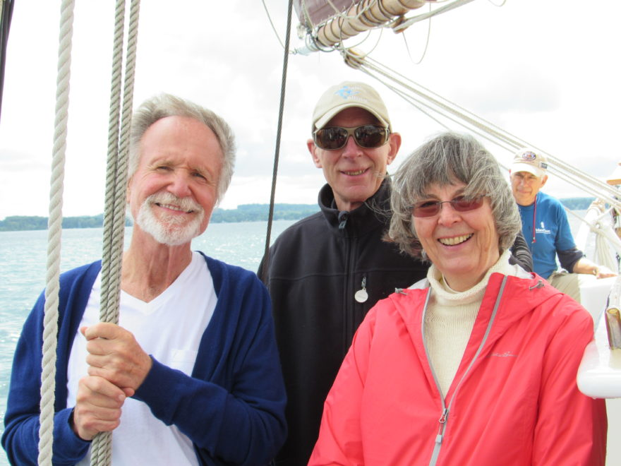 Three adults, one holding the ship's halyards, on a charter sail