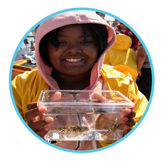 Girl holding fish in small tank on a family programs