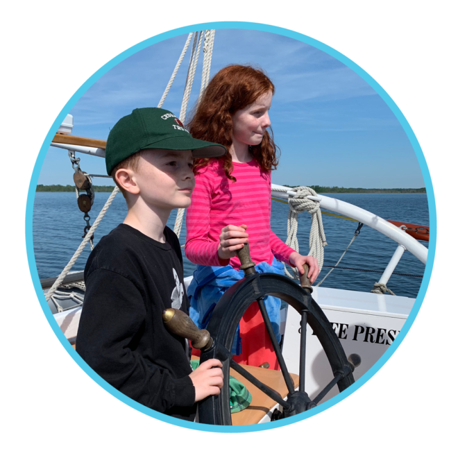 Youth steering the schooner on this science adventure sail