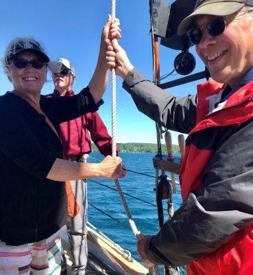 adults raising the sail