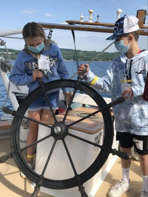 Youth steering ship with large tall ship wheel