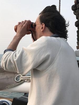 man on schooner looking through binoculars
