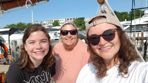three woman smiling on ship